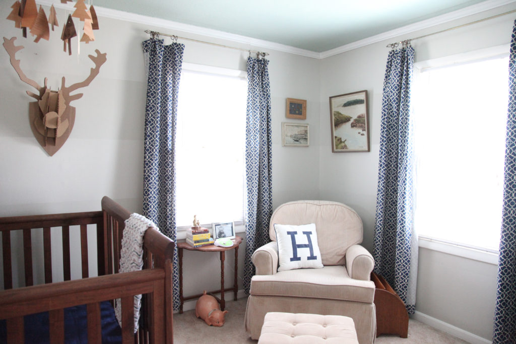 Gray on gray striped nursery with navy blue curtains, glider, cardboard taxidermy, and wood tree mobile