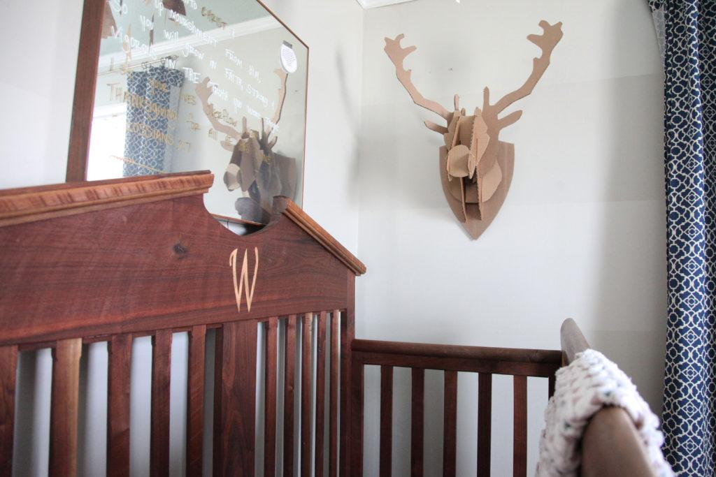 Custom made crib, DIY cardboard taxidermy, mid century mirror, navy blue Waverly curtains, chevron baby quilt, gray striped walls