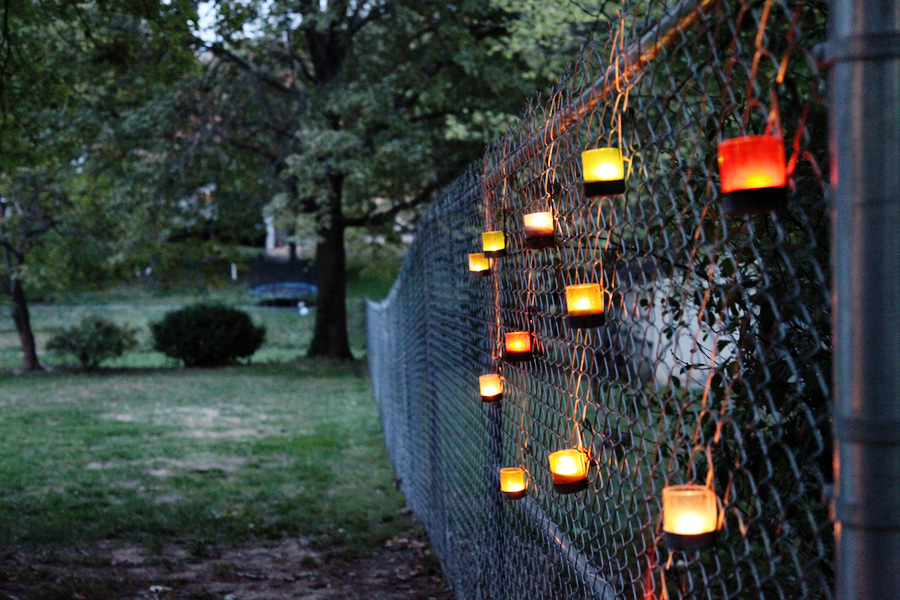 Tea lights on a chain link fence
