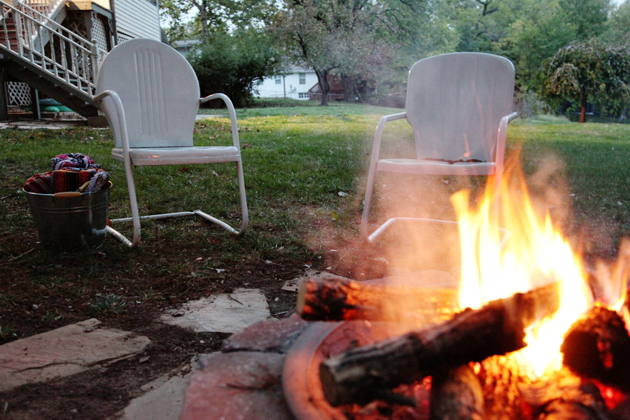 Vintage metal outdoor chairs sitting next to backyard firepit