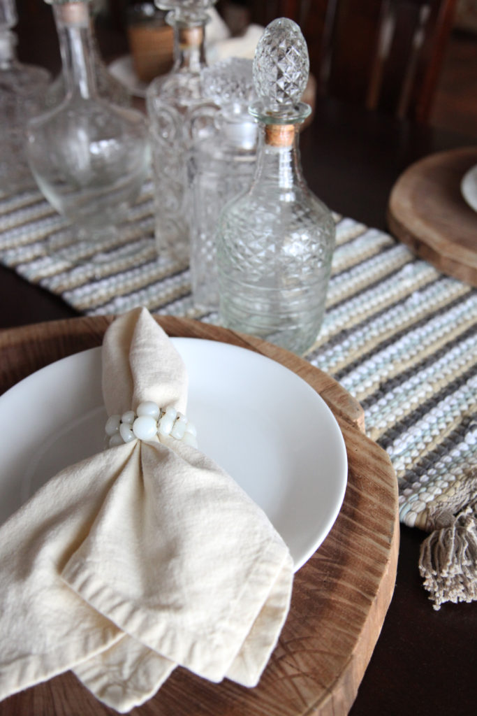 all white layered table setting with lots of texture wood charger layered with a while plate cream napkin and white stone napkin ring