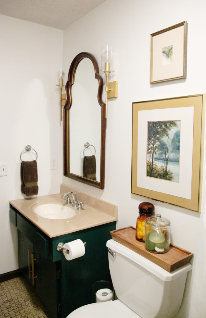 White green gold brown bathroom vanity with gold scones framed watercolors drop cloth shower curtain brown tile vintage mirror