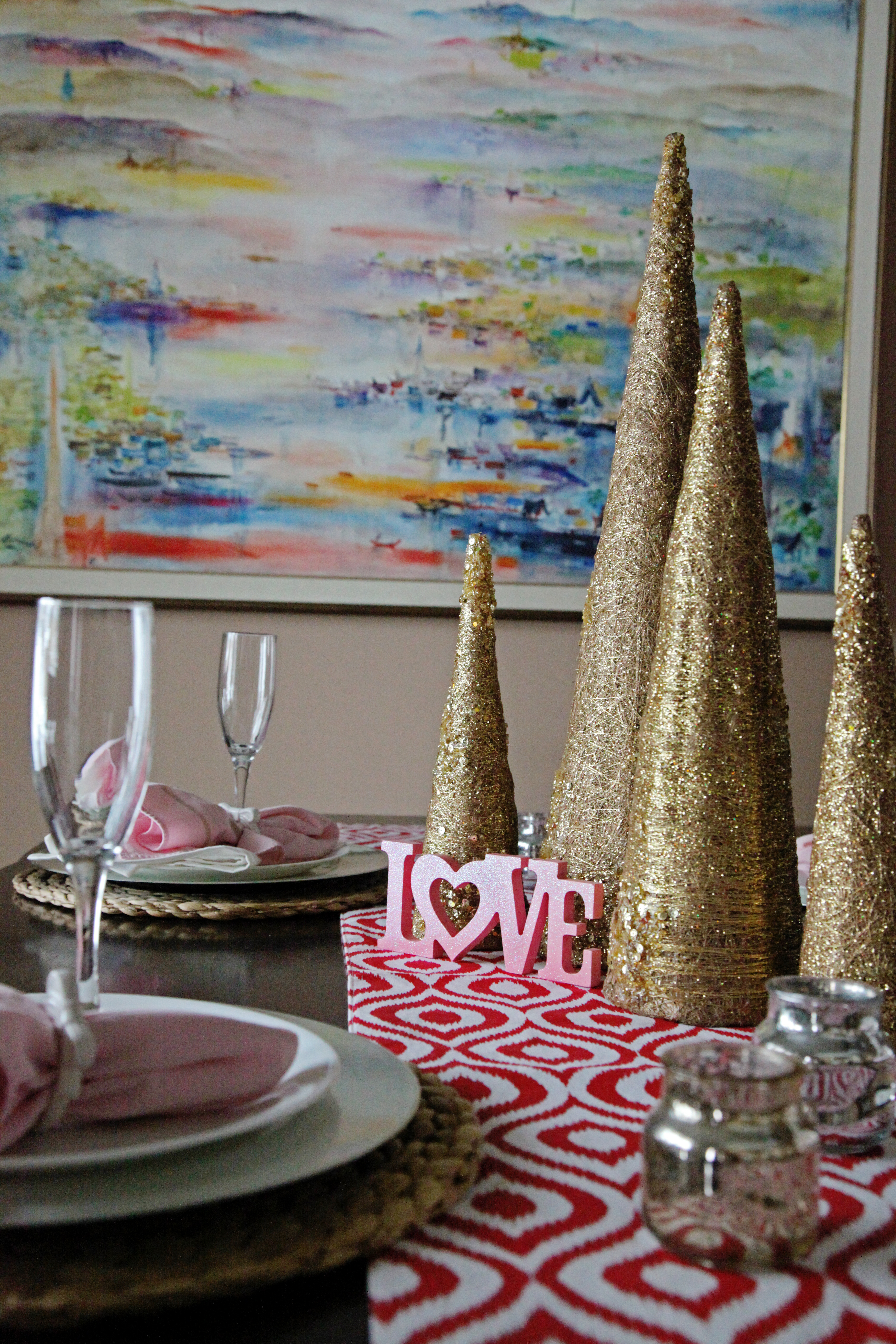 Valentines Day centerpiece using gold glitter christmas trees on top of a red ikat runner