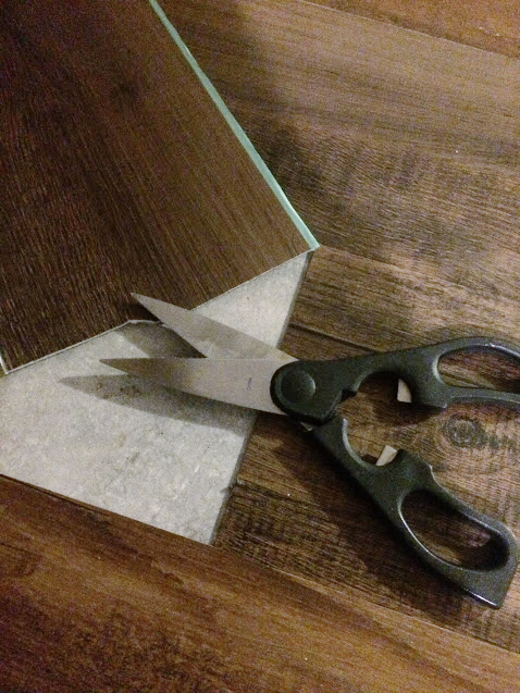 Using scissors to cut peel and stick tile