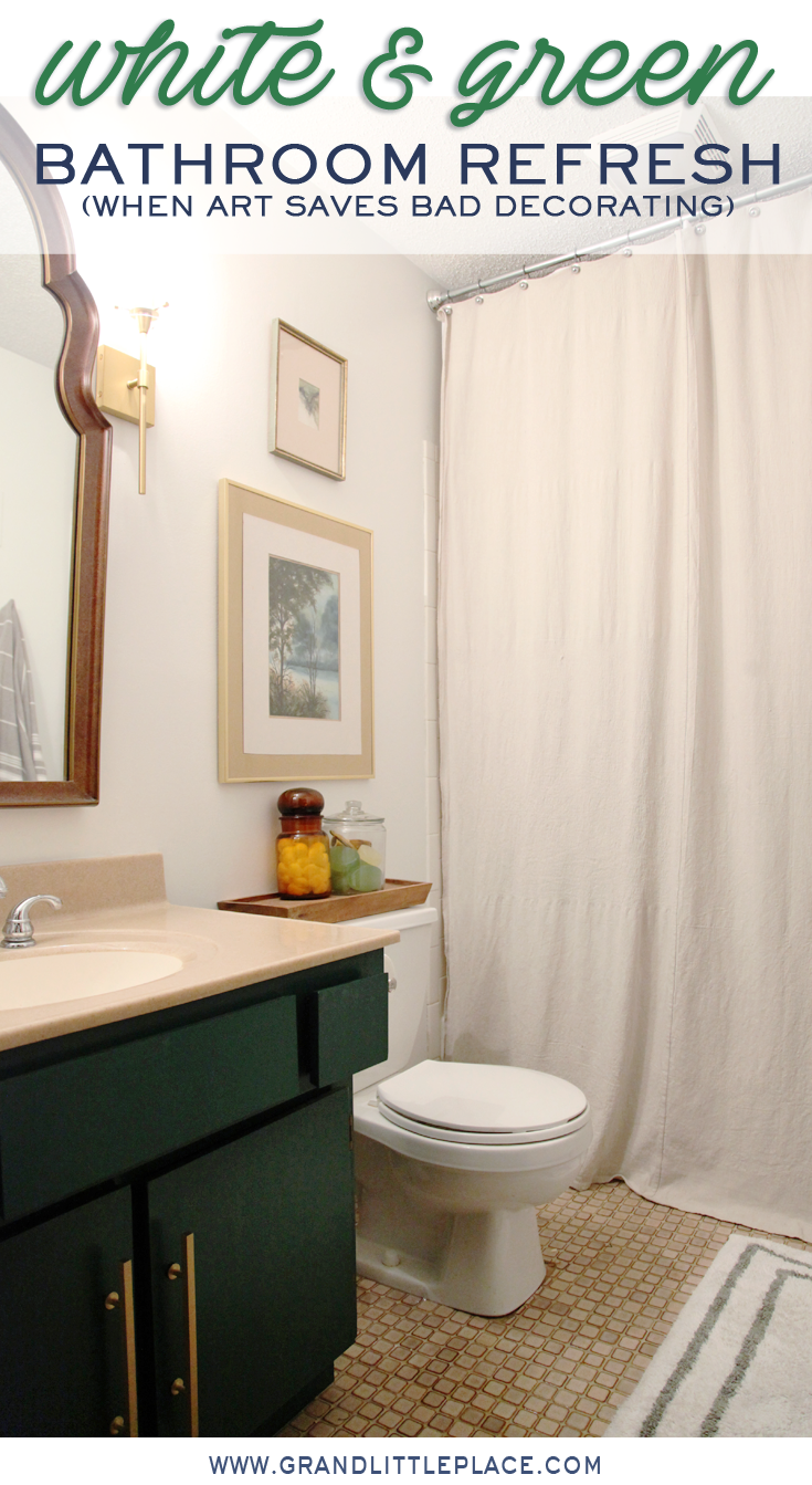 Bathroom painted white with green vanity gold hardware, vintage arched mirror, gold sconces, DIY drop cloth shower curtain and original artwork. Text overlay reads white and green bathroom refresh, when art helps bad decorating