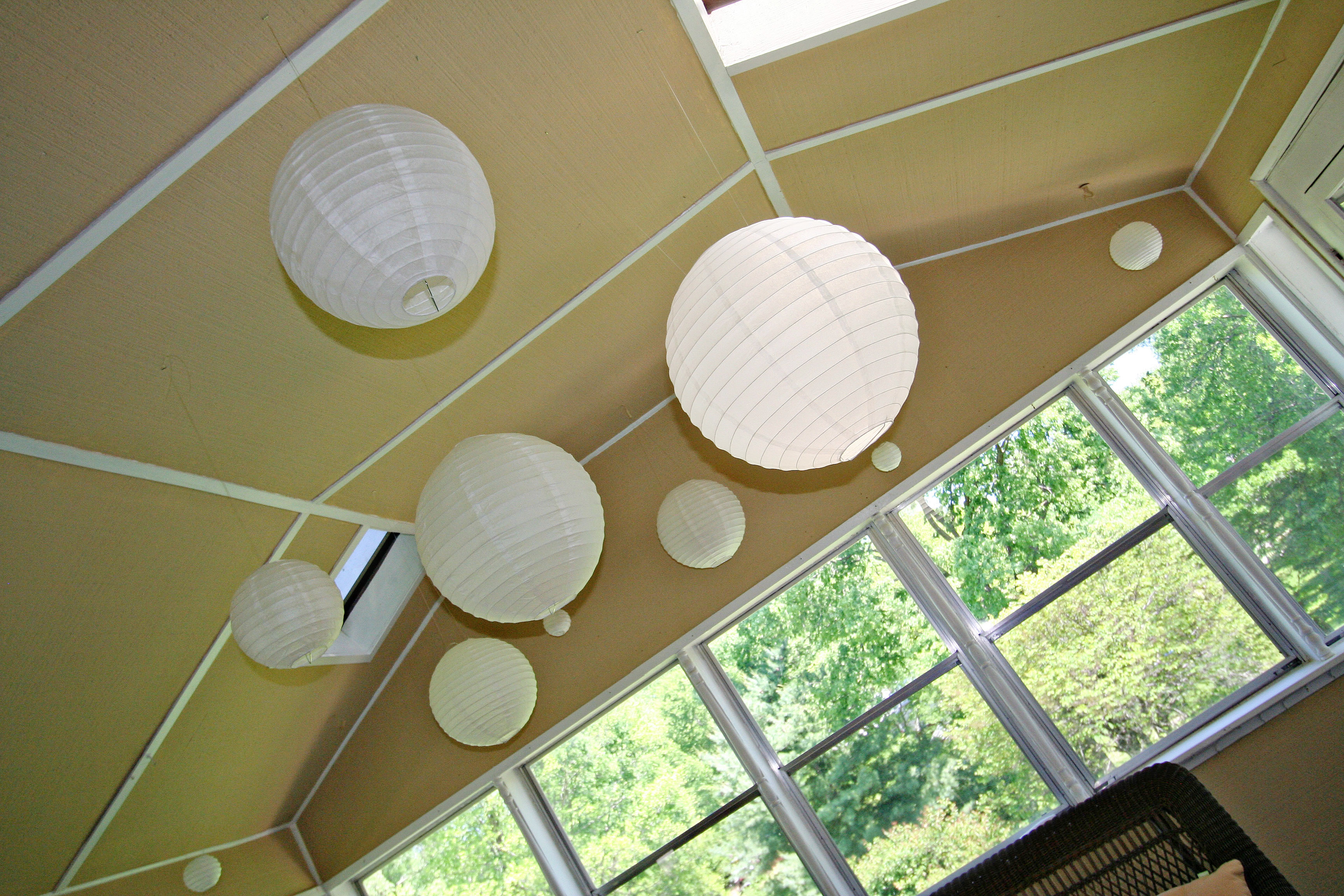 Paper lanterns hanging from sun room ceiling