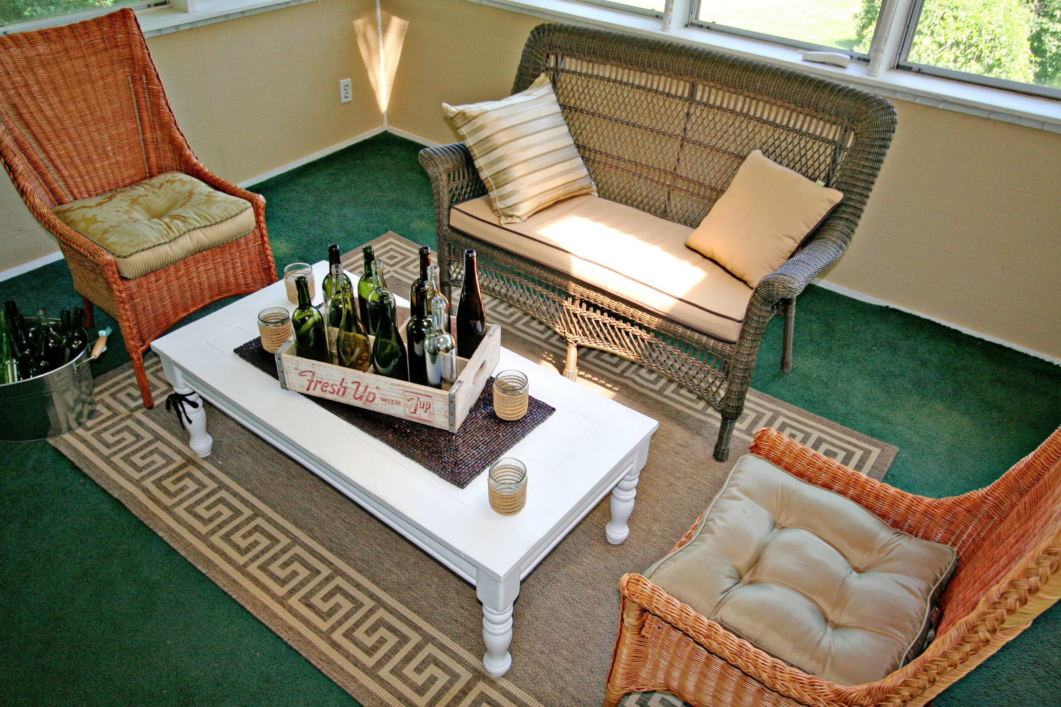 Sun room decor with white coffee table, wicker furniture, vintage soda crate with empty wine bottles and outdoor rug