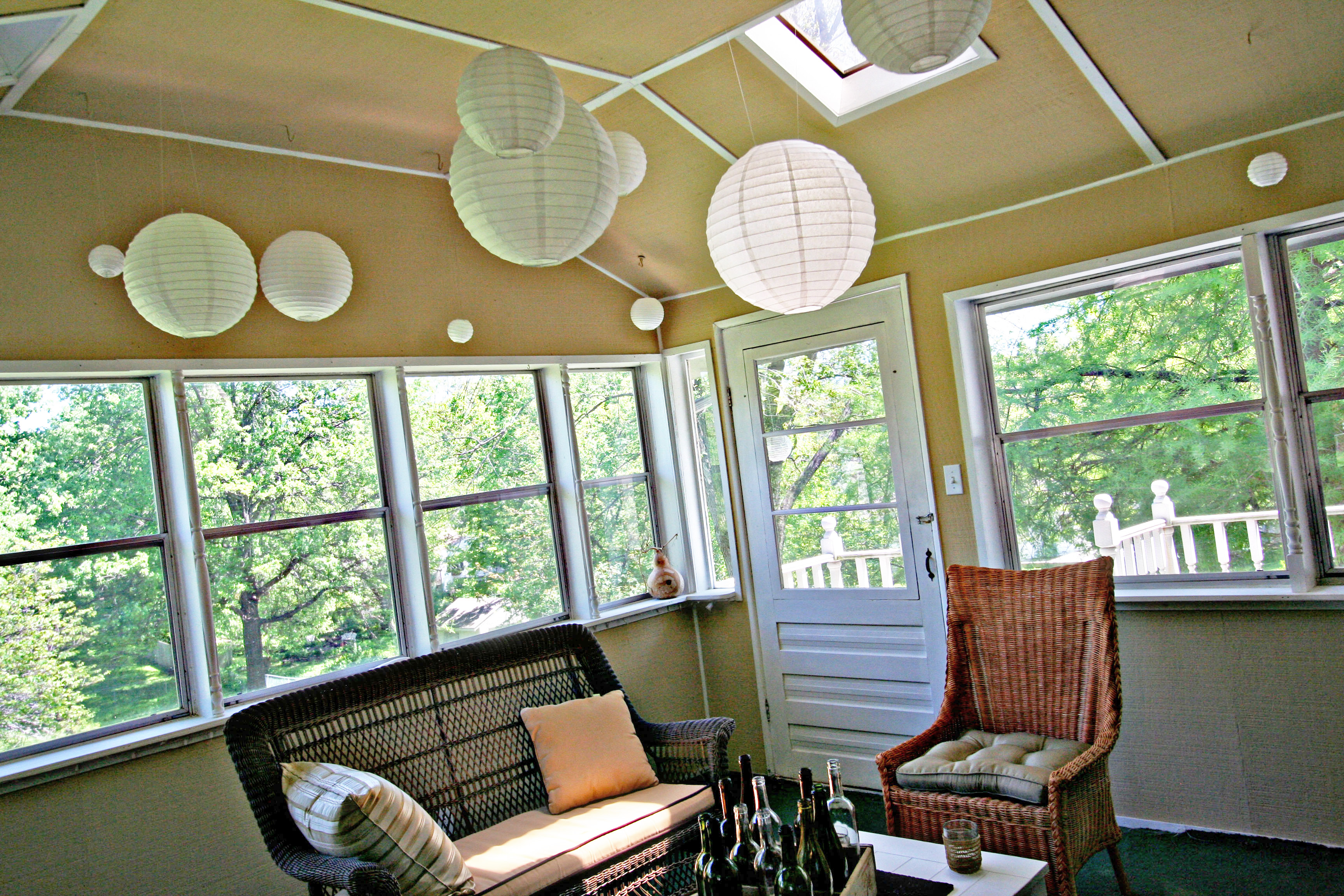 tan sun room with paper lanterns hanging from the ceiling