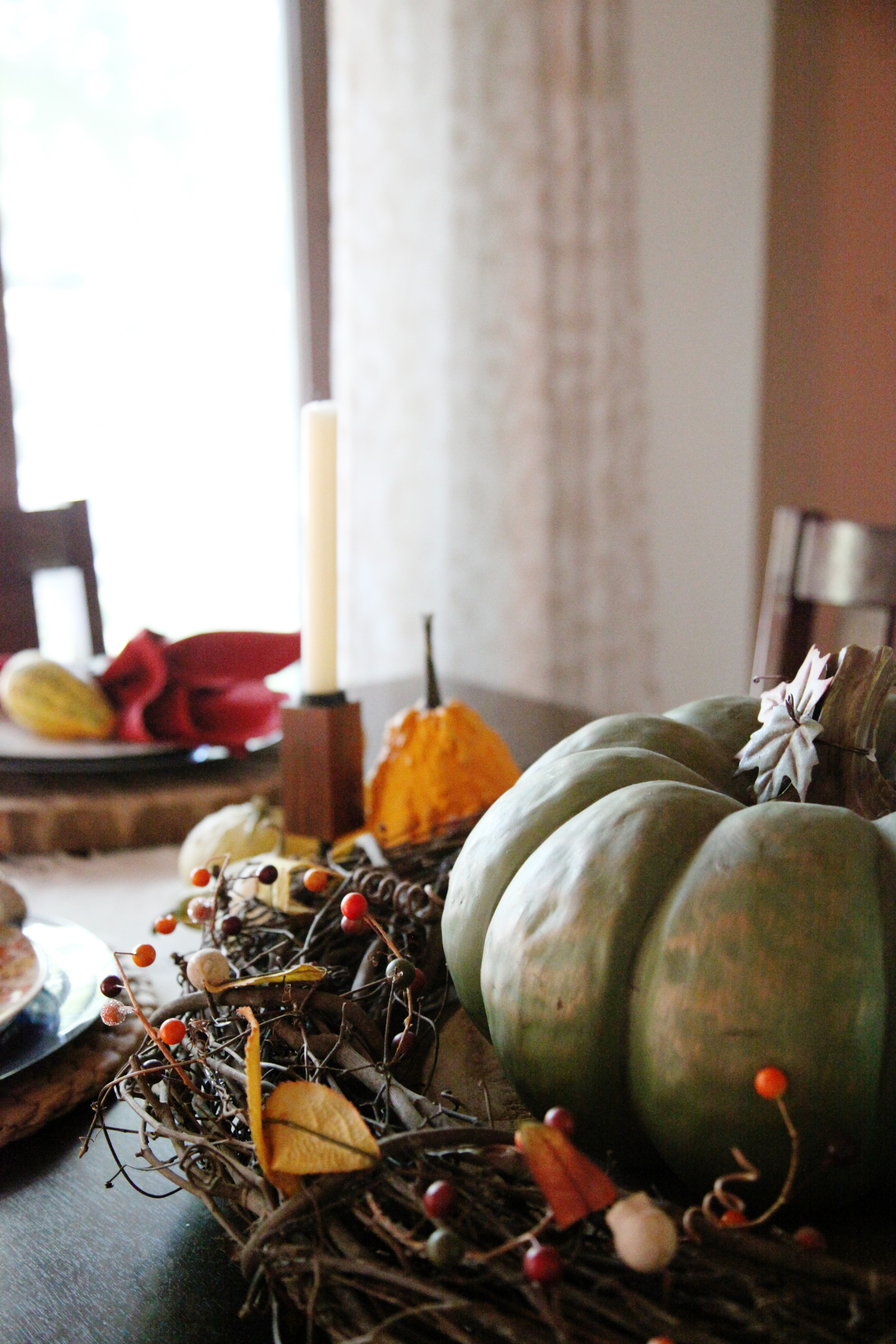 Up close detail of Thanksgiving Centerpiece with wood chargers, green cinderella pumpkin and a vine wreath