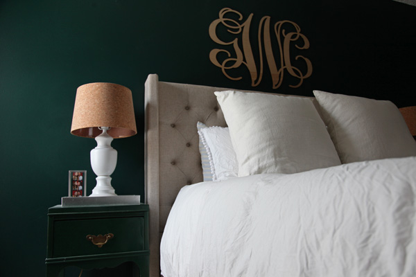 Master Bedroom with dark emerald green walls, linen tufted headboard, white pom pom trim duvet from INS COOL GIFTS, and  wood monogram wall hanging above the bed.  Nightstands have white lamps with cork shade.