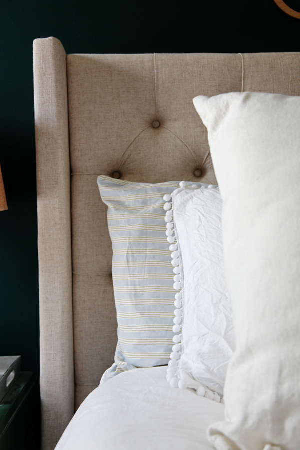 Close up of Queen Bed Headframe from Wayfair.  Natural Linen color tufted headboard.  Light blue and green striped sheets layered with white pom pom sham cover from INS COOL GIFTS layered with a white linen euro pillow from Ikea