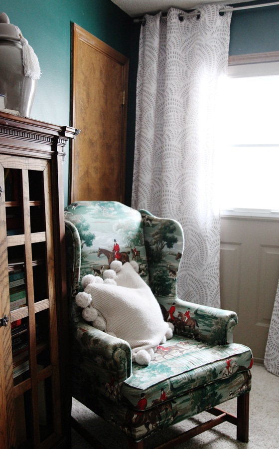 Equestrian green print wing back chairs with tan sweater pom pom trim pillow.  Curtains hanging in the background are white with a tan print grommet top from Kirklands.