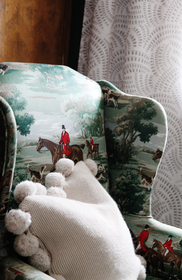 Equestrian print wingback chair in master bedroom with pom pom sweater pillow